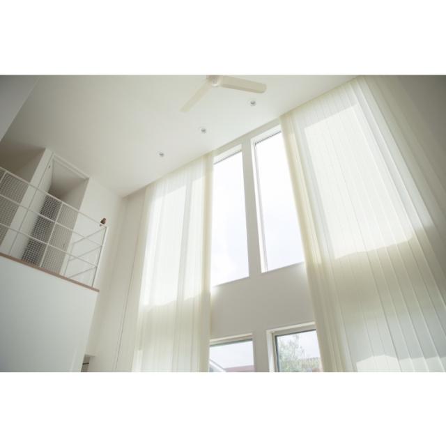迫力のあるブラインドが作る吹き抜けの窓際