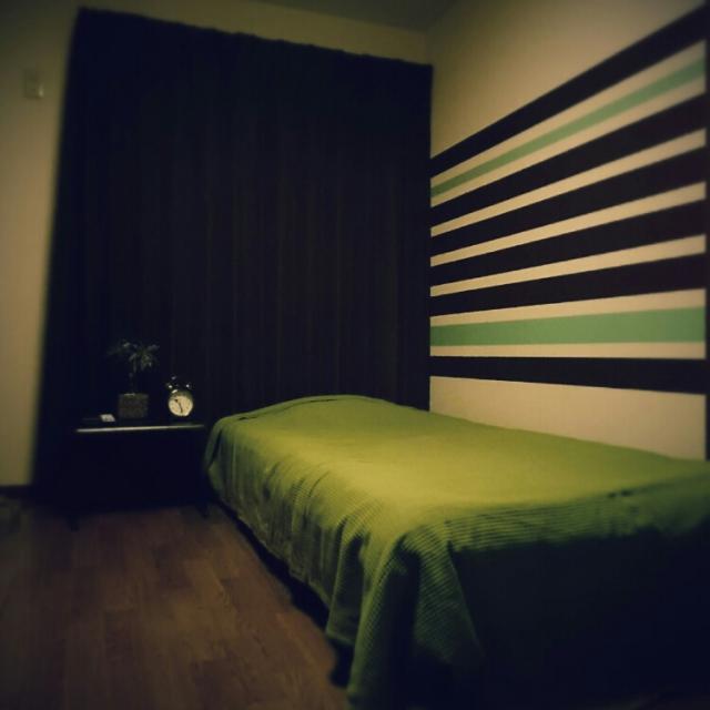 ベッドカバーと同系色のストライプの壁