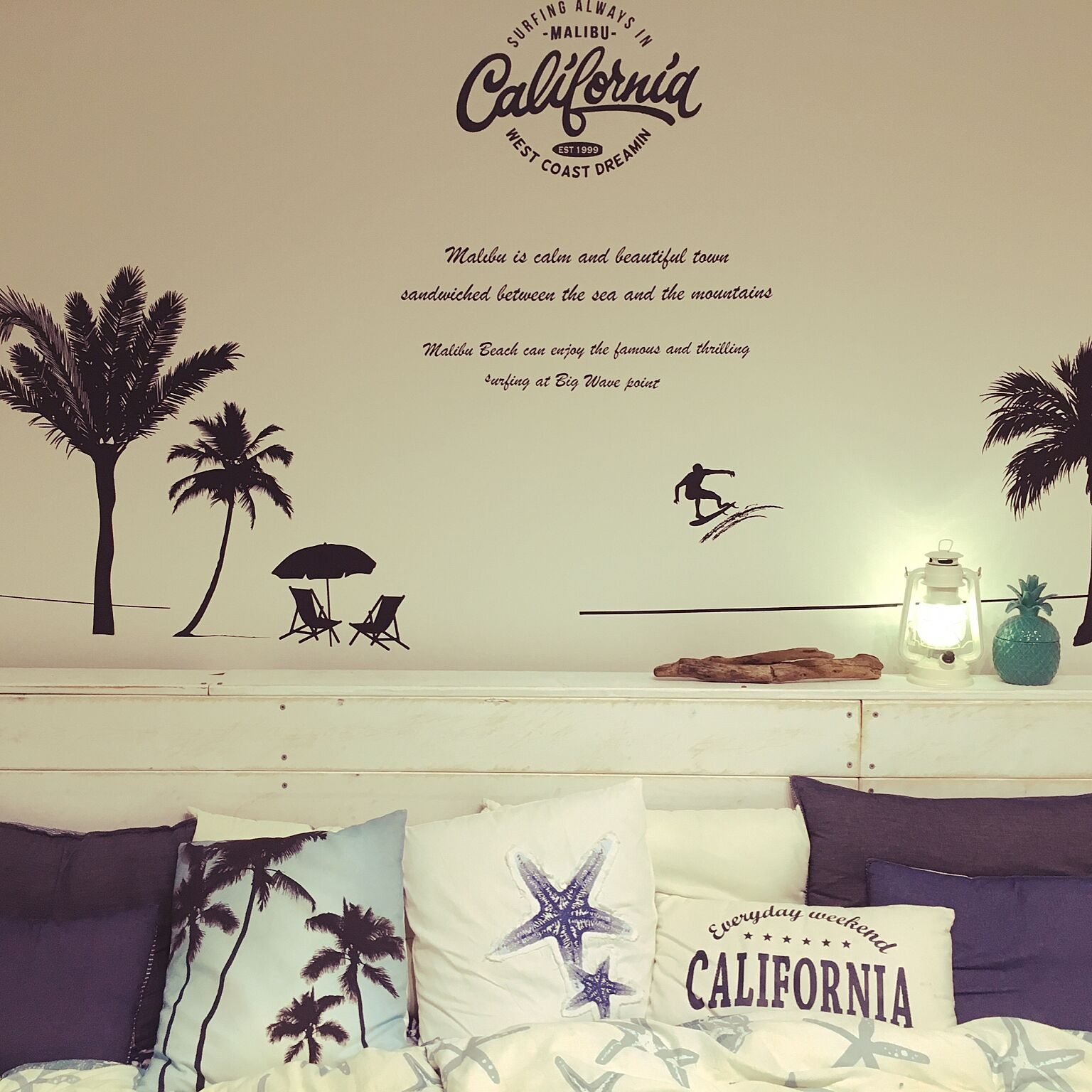 白い板を繋ぎ合わせて西海岸風のヘッドボードに。背後の壁にも海を感じる爽やかなベッドルームコーディネートです。